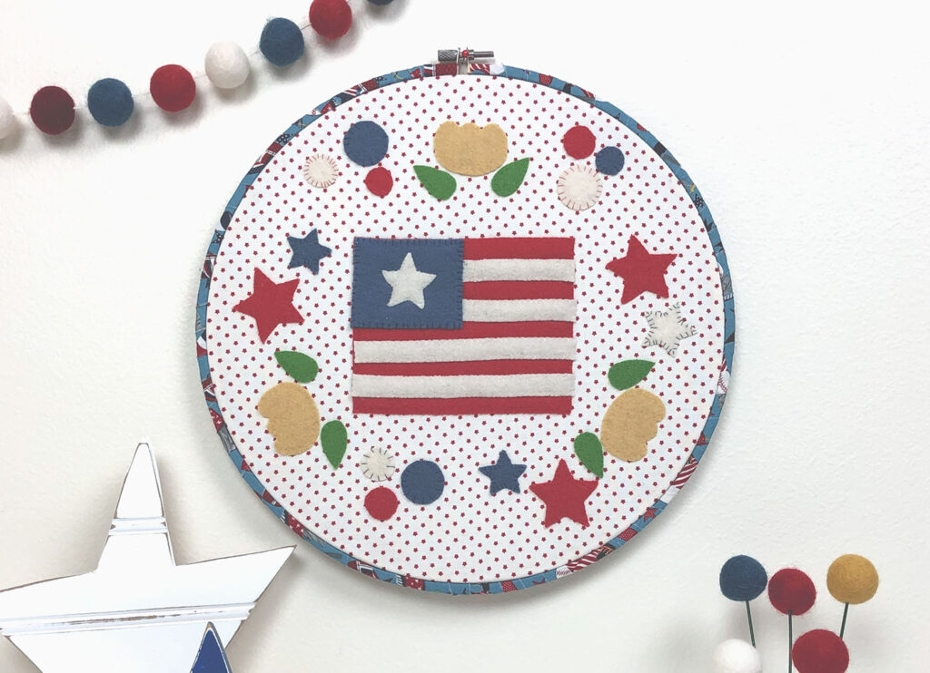 Flowers and stars surround a flag in this beautiful wool applique piece.