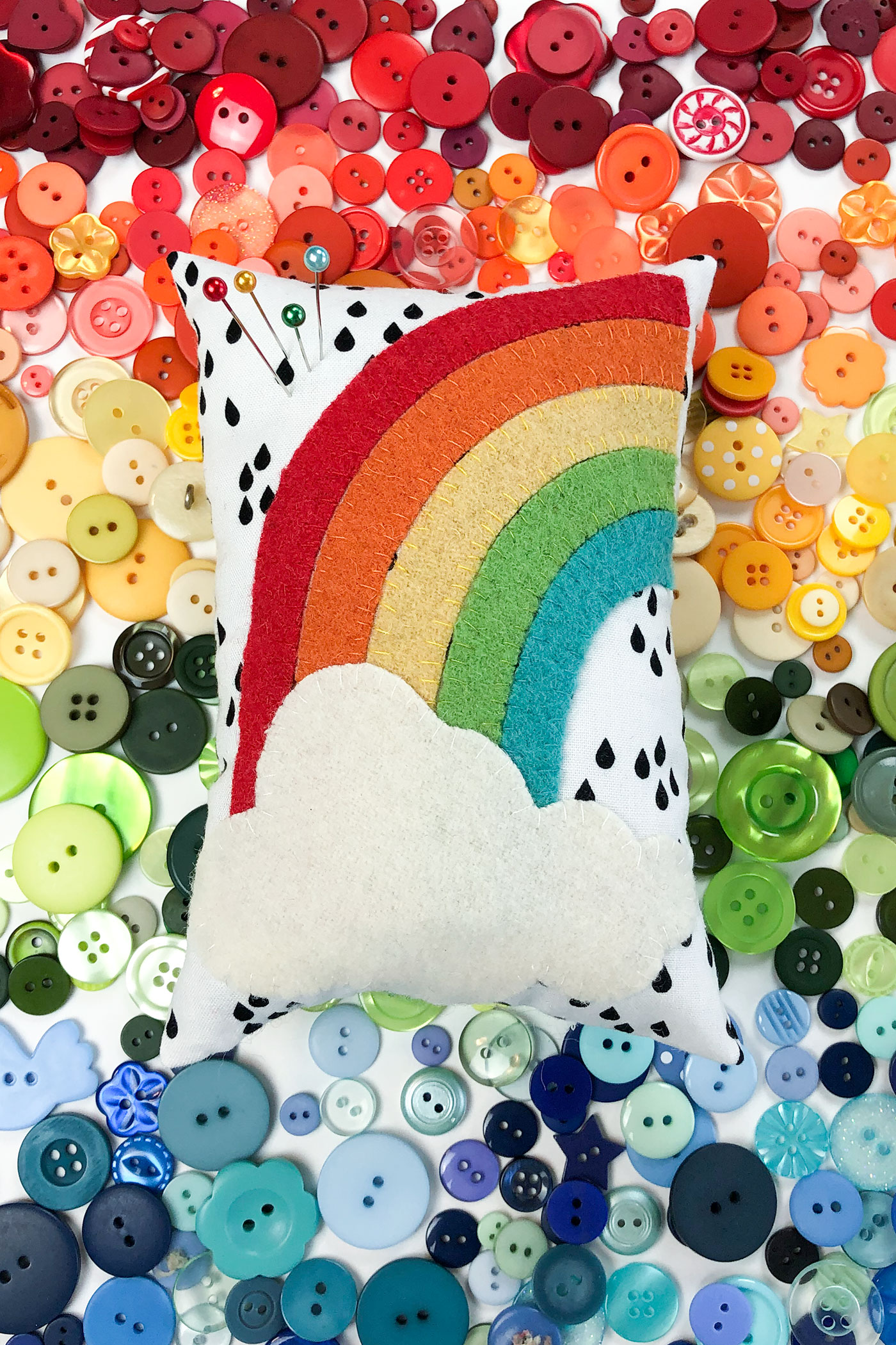 Pincushion with rainbow appliqued with wool on top of a rainbow of buttons.