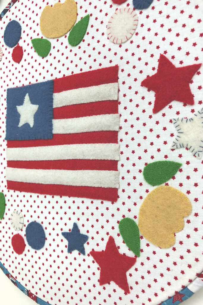 Flag, stars and flowers adorn this patriotic themed wool applique hoop.