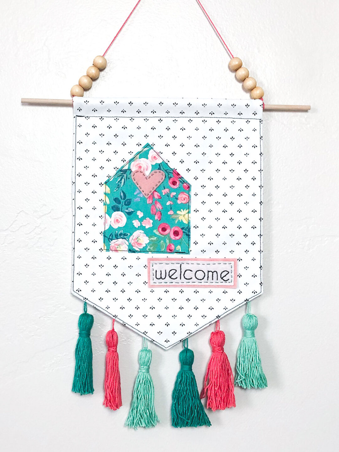 Welcome Wall Banner DIY by top US sewing blog Ameroonie Designs: image shows the finished welcome banner with floral cottage and embellishments