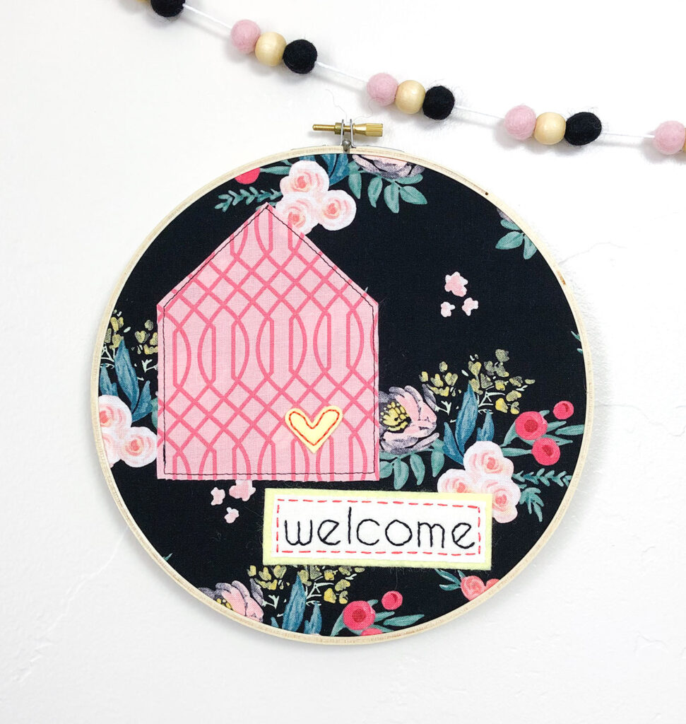 Welcome Wall Banner DIY featured by Top US sewing blog Ameroonie Designs: image of welcome banner embellishments finished in embroidery hoop as alternative for finishing