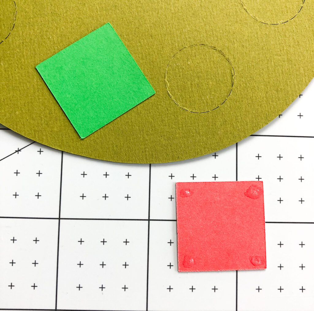 Personalized Christmas Countdown featured by top US craft blog Ameroonie Designs: Image of gluing colored squares to back of perforated circle