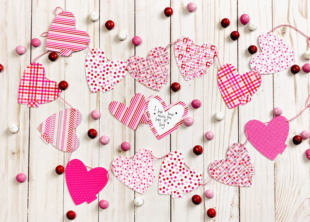 DIY Valentine Countdown Banner featured by top US craft blog Ameroonie Designs: image of paper heart banner with hidden love notes.