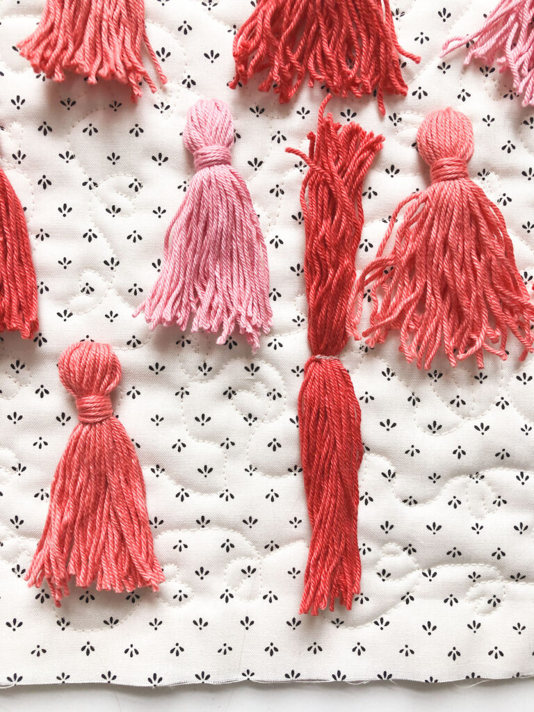 Tassel Pillow DIY featured by top US sewing blog Ameroonie Designs: image of tassel threads sewn down to pillow front.