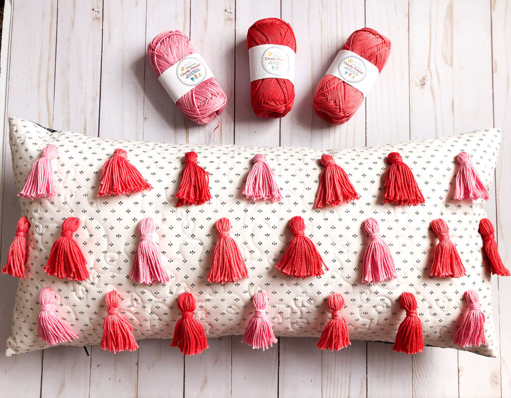 Tassel Pillow DIY featured by top US sewing blog Ameroonie Designs: Image of Tassel pillow with chunky thread tassels.