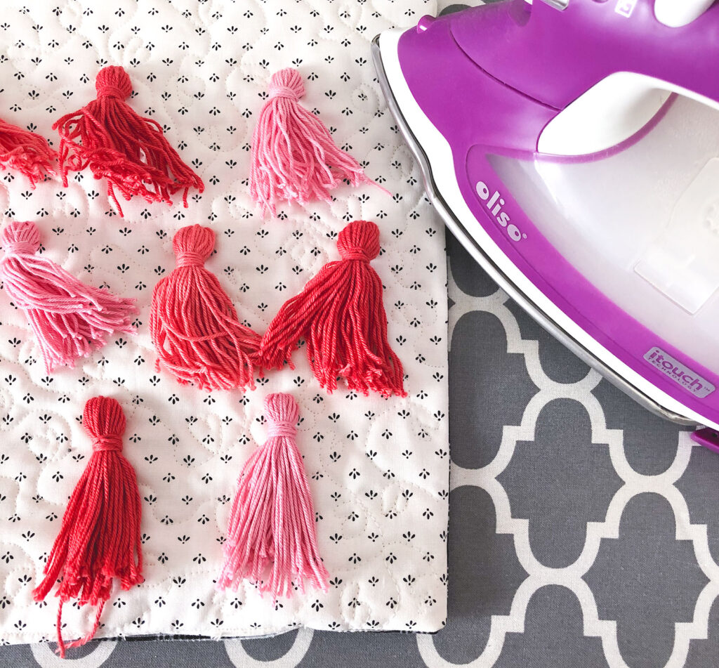 Tassel Pillow DIY featured by top US sewing blog Ameroonie Designs: image of steaming the threads to straighten them.