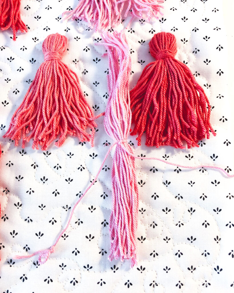 Tassel Pillow DIY featured by top US sewing blog Ameroonie Designs: image of threads cut to prepare to create tassel.