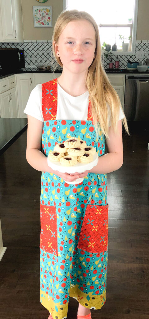 Crossback Apron Tutorial by Top US sewing blog Ameroonie Designs: image of a girl wearing a cross back apron