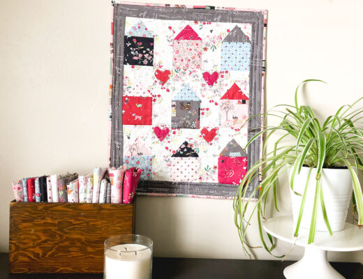Community Love Mini quilt by Top US sewing blog Ameroonie Designs. Image of: mini quilt with houses and hearts.