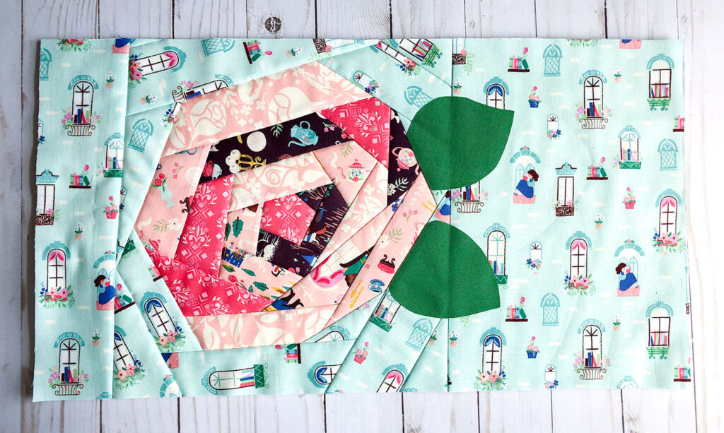 QAYG Rose Reading Pillow by top US sewing blog Ameroonie Designs. Image of: adding background and leaves to the QAYG rose on the pocket.