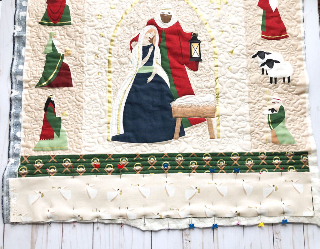 Advent Mini Quilt by top US sewing blog Ameroonie Designs. Image of: adding pockets to bottom of quilted mini quilt.