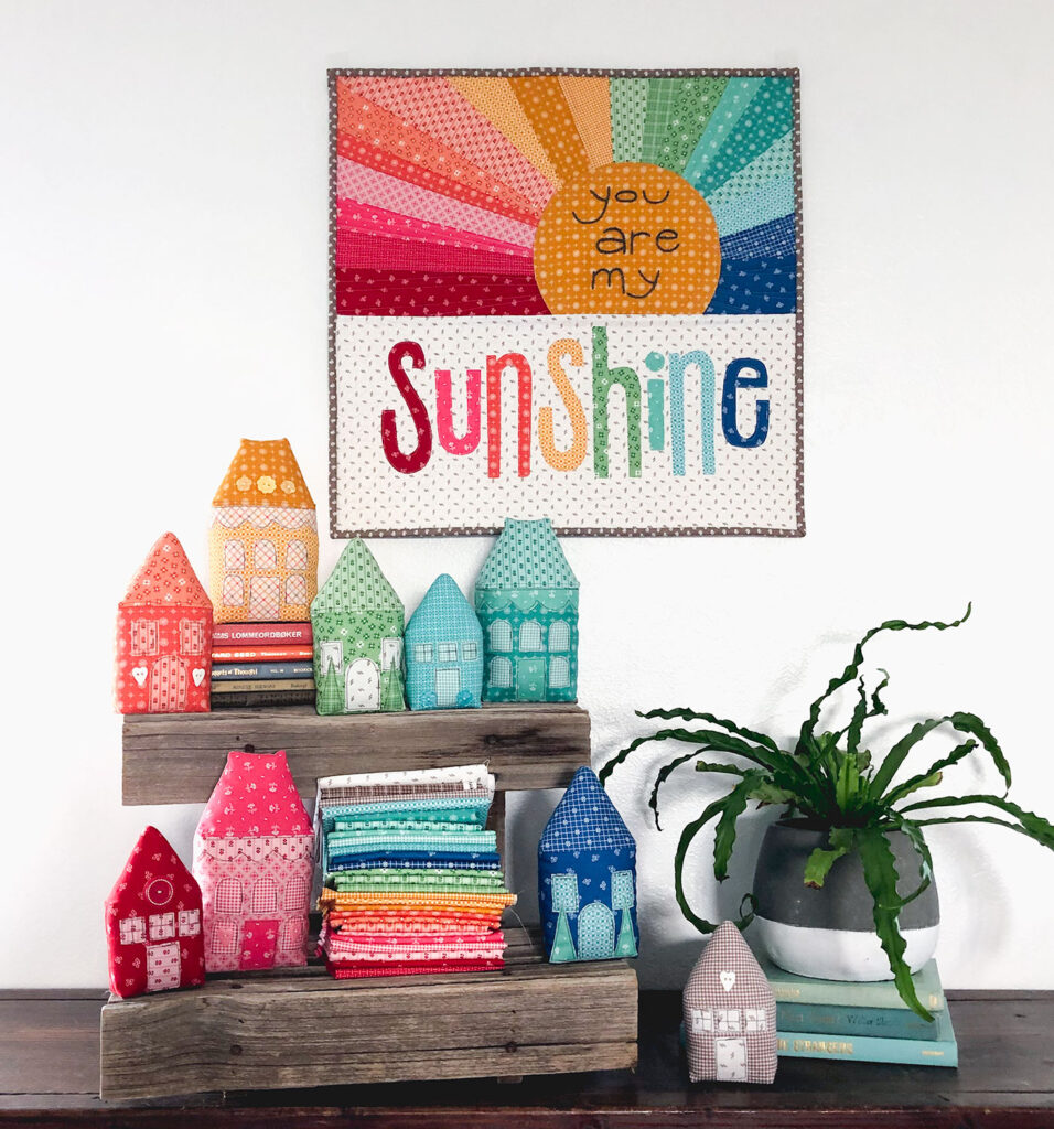 Rainbow Village with Prim fabric by Top US sewing blog Ameroonie Designs: image of Rainbow Sunshine mini quilt and fabric houses.