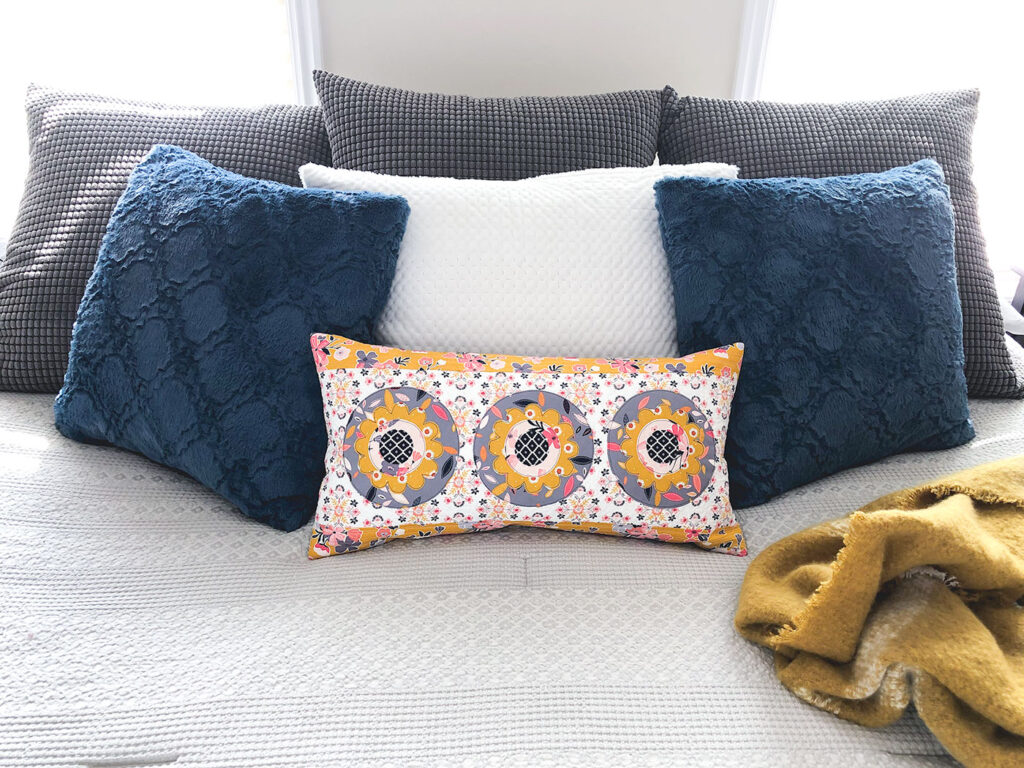 Simple and stunning raw-edge applique by Top US sewing blog Ameroonie Designs. Image of: lumbar pillow on bed.