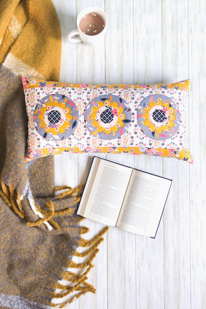 Simple and stunning raw-edge applique by Top US sewing blog Ameroonie Designs. Image of: lumbar pillow with book and hot cocoa