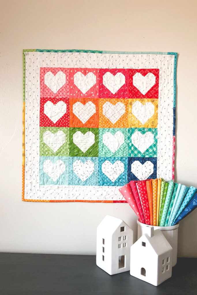 Heart Mini Quilt by top US sewing blog Ameroonie Designs. Image of:Mini quilt with rainbow hearts and fabric.