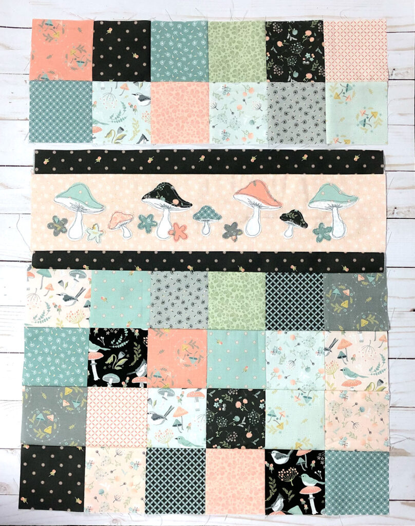 Patchwork doll quilt by top US sewing blog Ameroonie Designs. Image of sewing patchwork blocks to applique strip.