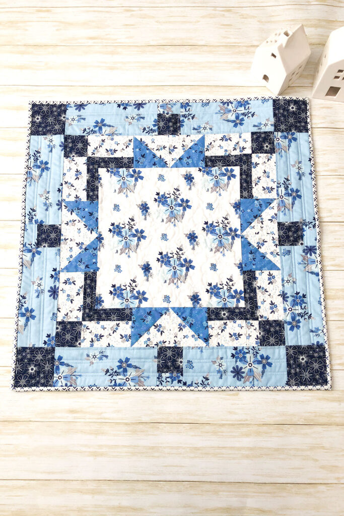 Easy table topper quilt by Top US sewing blog Ameroonie Designs. Image of: table topper with ceramic houses.