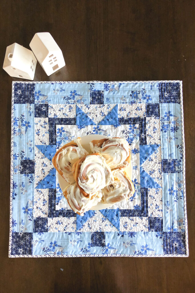 Easy table topper quilt by Top US sewing blog Ameroonie Designs. Image of: table topper with cinnamon rolls.