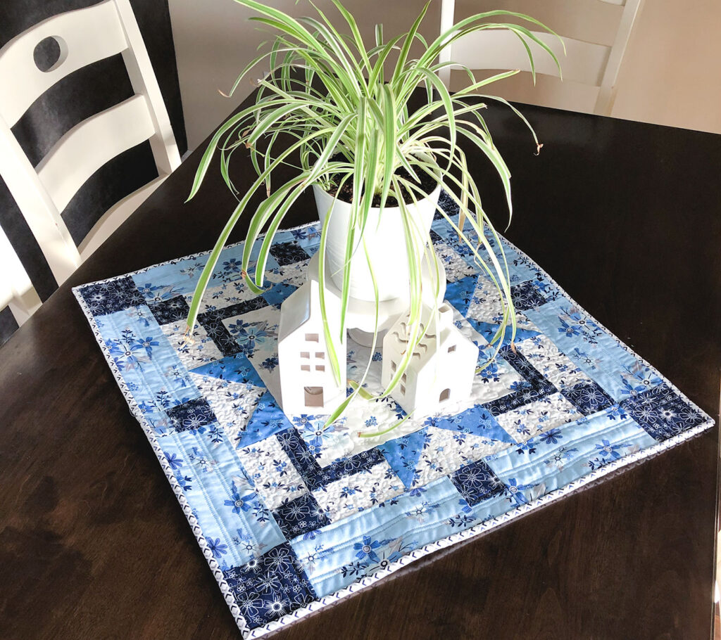 Easy table topper quilt by Top US sewing blog Ameroonie Designs. Image of: table topper with plant and houses.