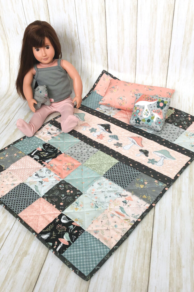 Patchwork doll quilt by top US sewing blog Ameroonie Designs. Image of doll with quilt and pillows.