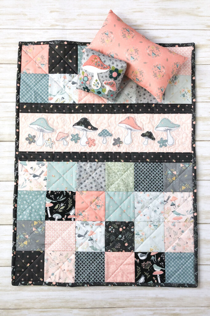 Patchwork doll quilt by top US sewing blog Ameroonie Designs. Image of doll quilt with applique strip and pillows.