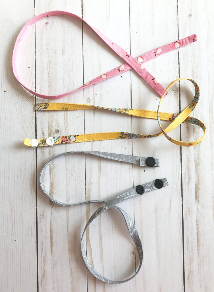 Accessorize your face mask tutorials by top US sewing blog Ameroonie Designs. Image of sewing mask straps and adding snaps.