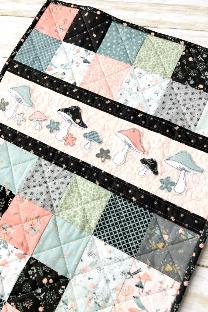 Patchwork doll quilt by top US sewing blog Ameroonie Designs. Image of close up of applique on patchwork doll quilt.