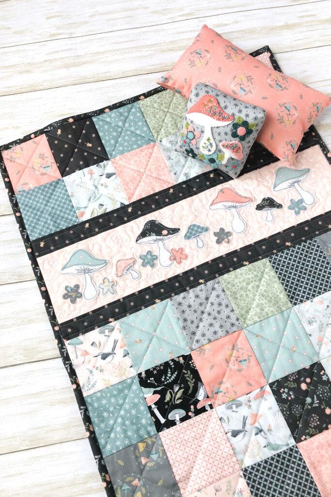 Patchwork doll quilt by top US sewing blog Ameroonie Designs. Image of doll quilt and pillows close up.