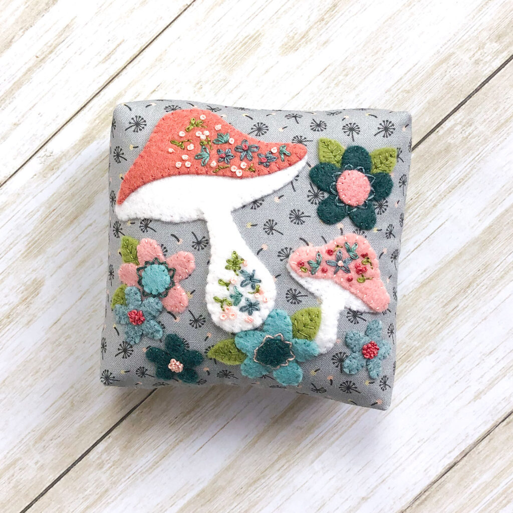 Patchwork doll quilt by top US sewing blog Ameroonie Designs. Image of applique pillow.
