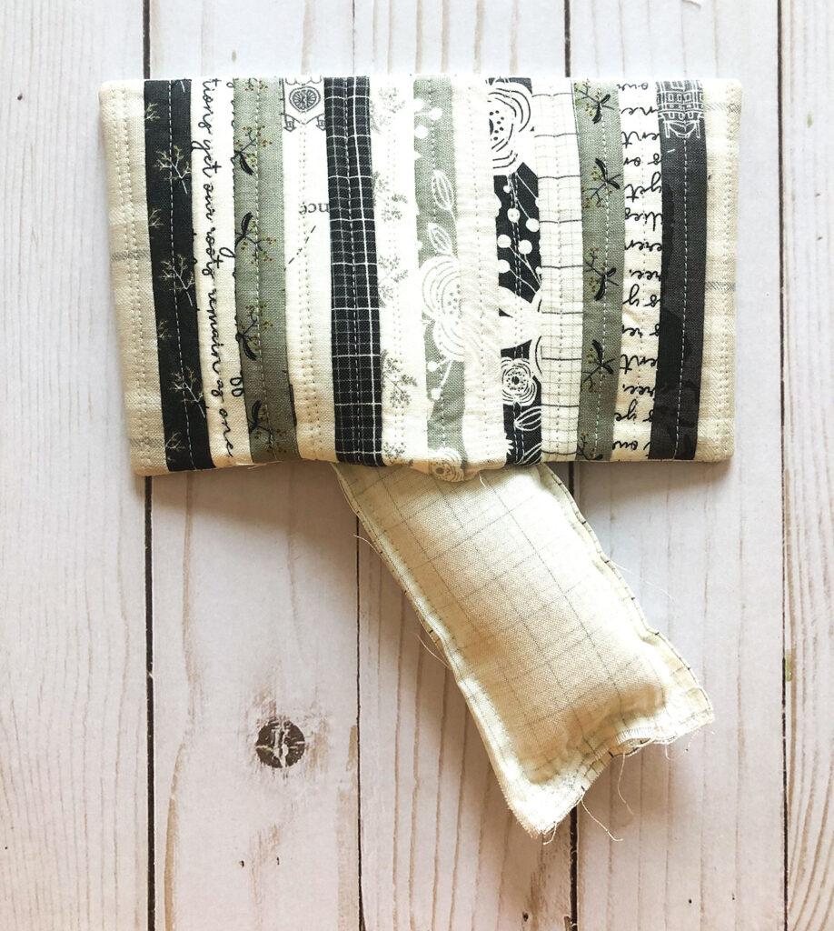 Scraptastic and simple Strip Pincushion by top US sewing blog Ameroonie Designs. Image of: inserting weight into pincushion.