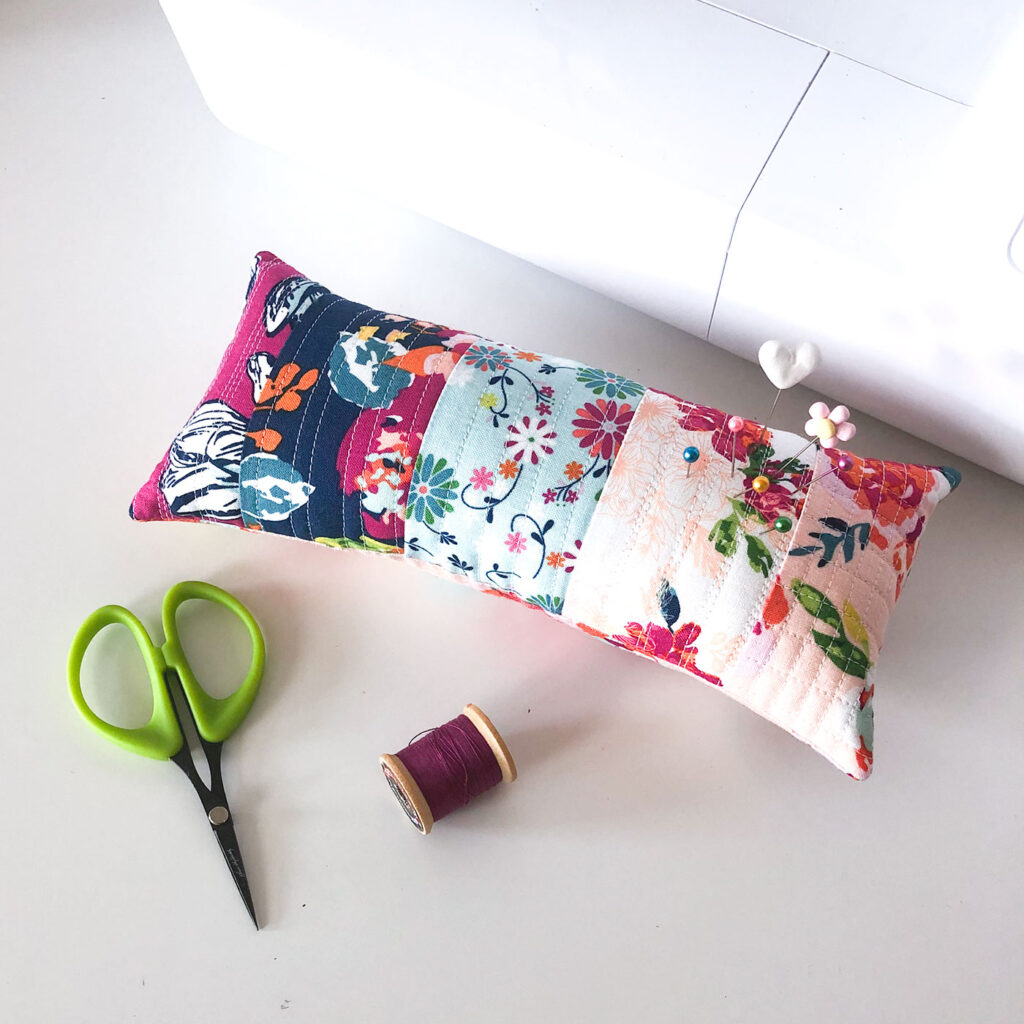Scraptastic and simple Strip Pincushion by top US sewing blog Ameroonie Designs. Image of: colorful pincushion with sewing machine.