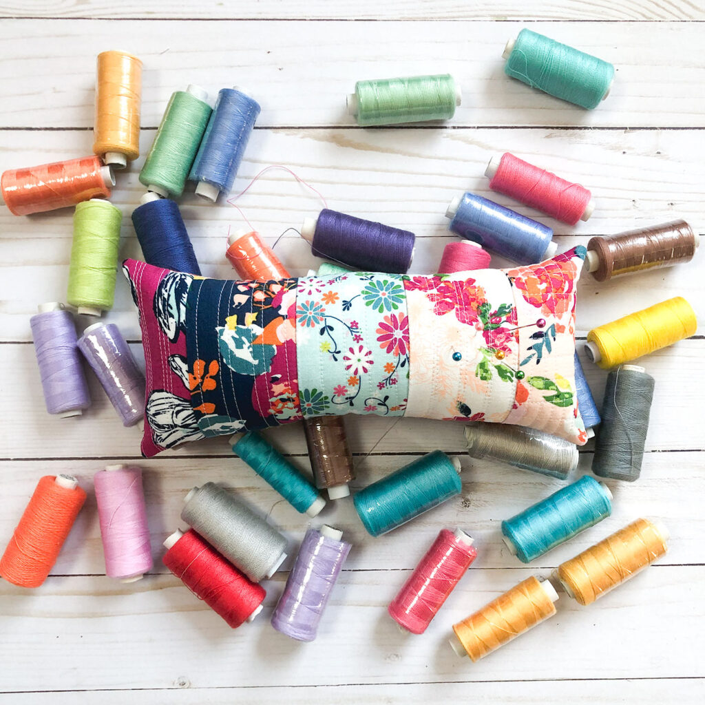 Scraptastic and simple Strip Pincushion by top US sewing blog Ameroonie Designs. Image of: colorful pincushion on thread.