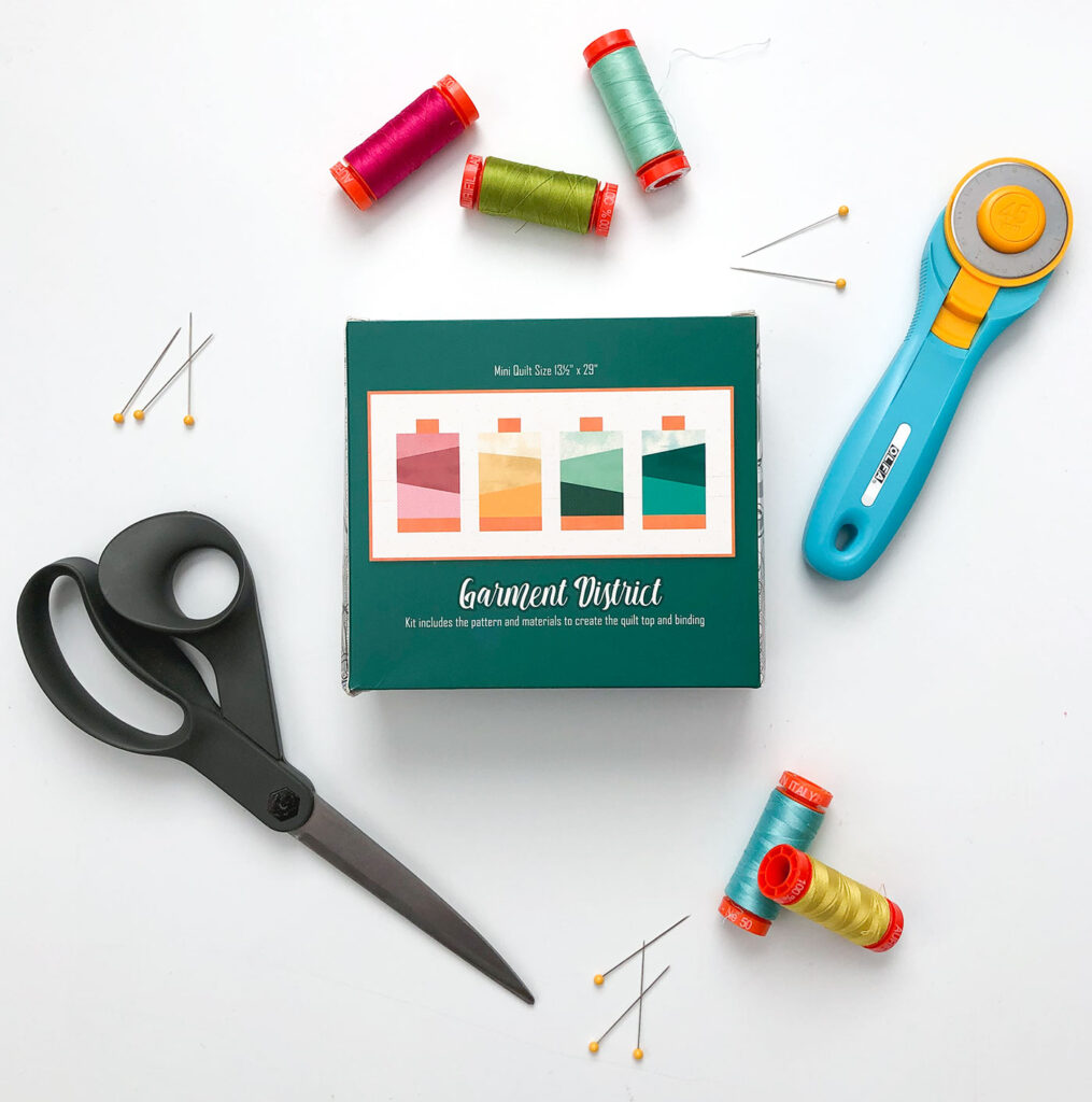 Garment District mini quilt kit surrounded by sewing supplies including pins and thread.
