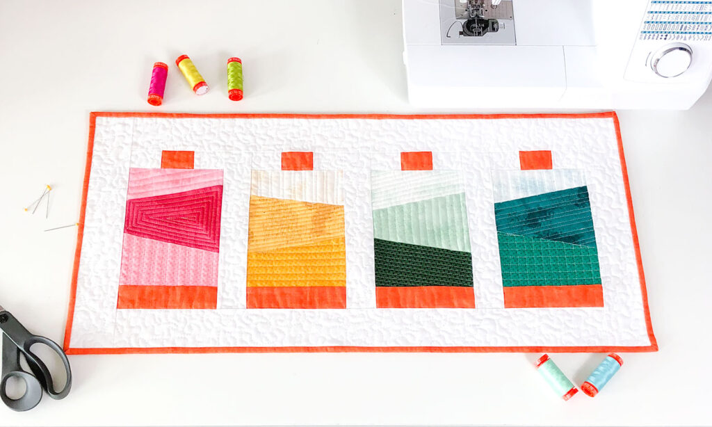 Thread spools create a sewing themed mini quilt.