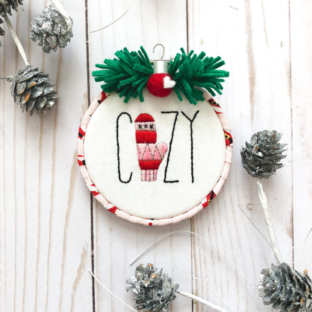 Customized Embroidered Ornaments by Top US craft blog Ameroonie Designs. Image of COZY ornament with pine cones.