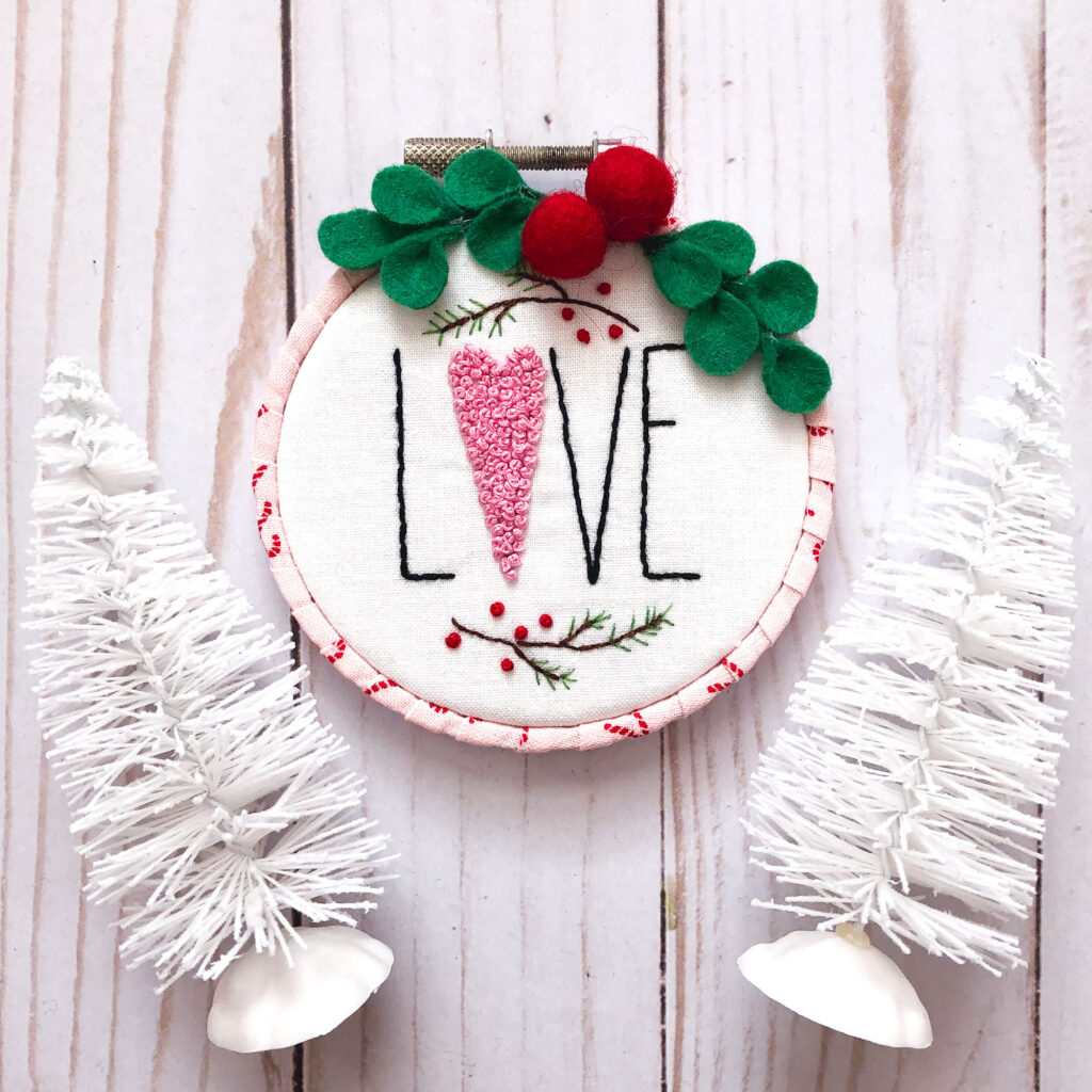 Customized Embroidered Ornaments by Top US craft blog Ameroonie Designs. Image of LOVE ornament with white trees.