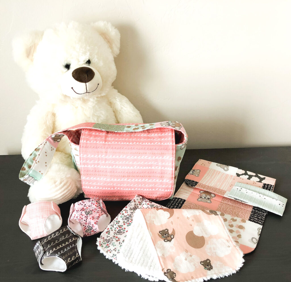 Pretend Play Diaper bag with top US sewing blog Ameroonie Designs. Image of teddy bear with diaper bag and accessories.