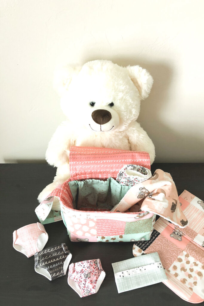 Pretend Play Diaper bag with top US sewing blog Ameroonie Designs. Image of teddy bear with diaper bag accessories and bag.
