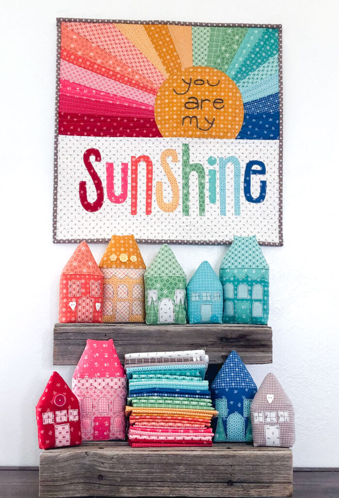 Rainbow Sunshine mini quilt sew along with top US sewing blog Ameroonie Designs. Image of mini quilt and houses with fabric.