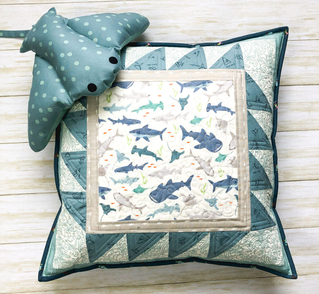 Shark teeth pillow by top US sewing blog Ameroonie Designs. Image of quilted pillow with Manta Shark stuffed pillow.