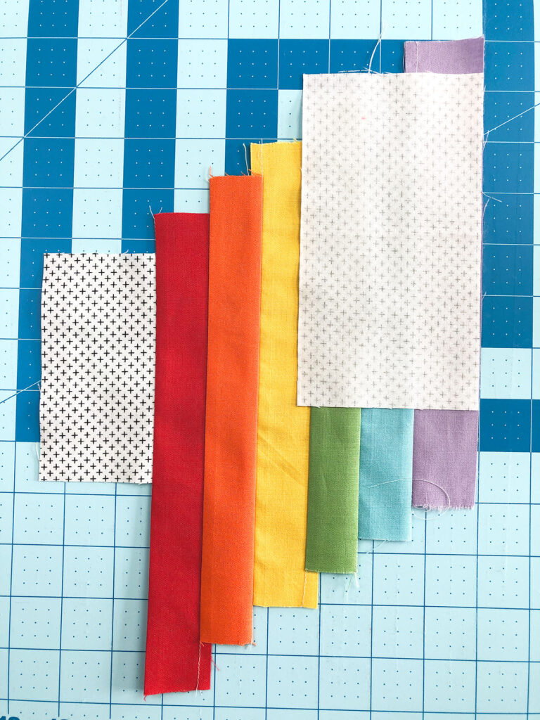 Wide Stripe Modern Rainbow mug rug tutorial by top US sewing blog Ameroonie Designs. Image of adding final background piece to mug rug front.