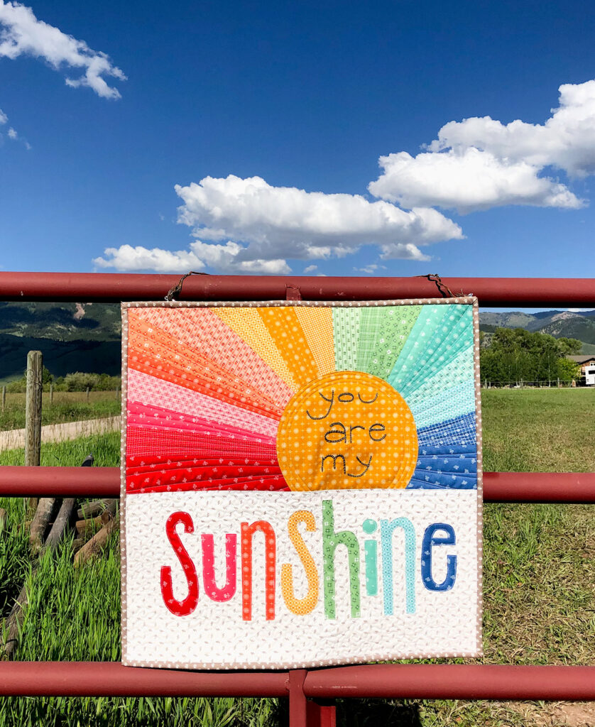 Rainbow Sunshine mini quilt sew along with top US sewing blog Ameroonie Designs. Image of mini quilt on barn fence and sky.