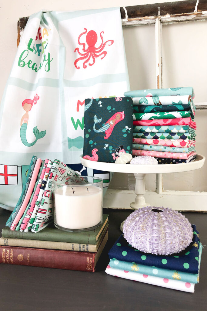 Sew a beautiful colored pencil pouch with top US sewing blog Ameroonie Designs. Image of Ahoy Mermaids fabric with sea urchin shells and books.