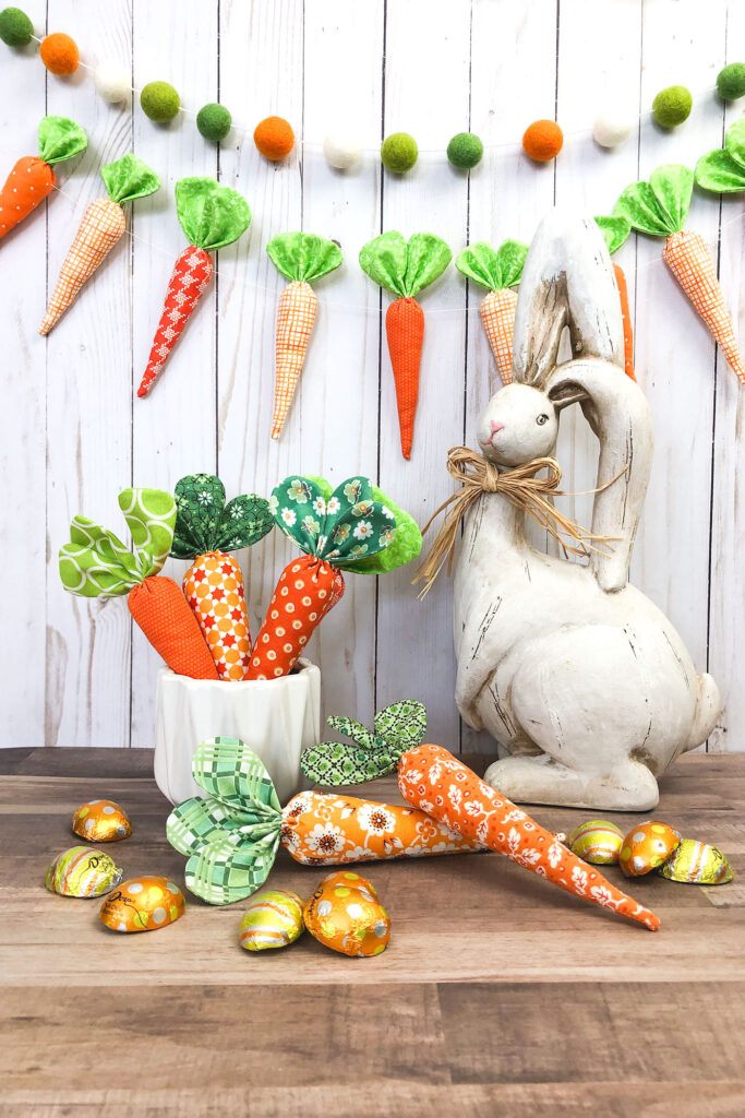 How to sew fabric carrots with top US sewing blog Ameroonie Designs. Image of cement bunny with fabric carrot garland and carrots in buckets.