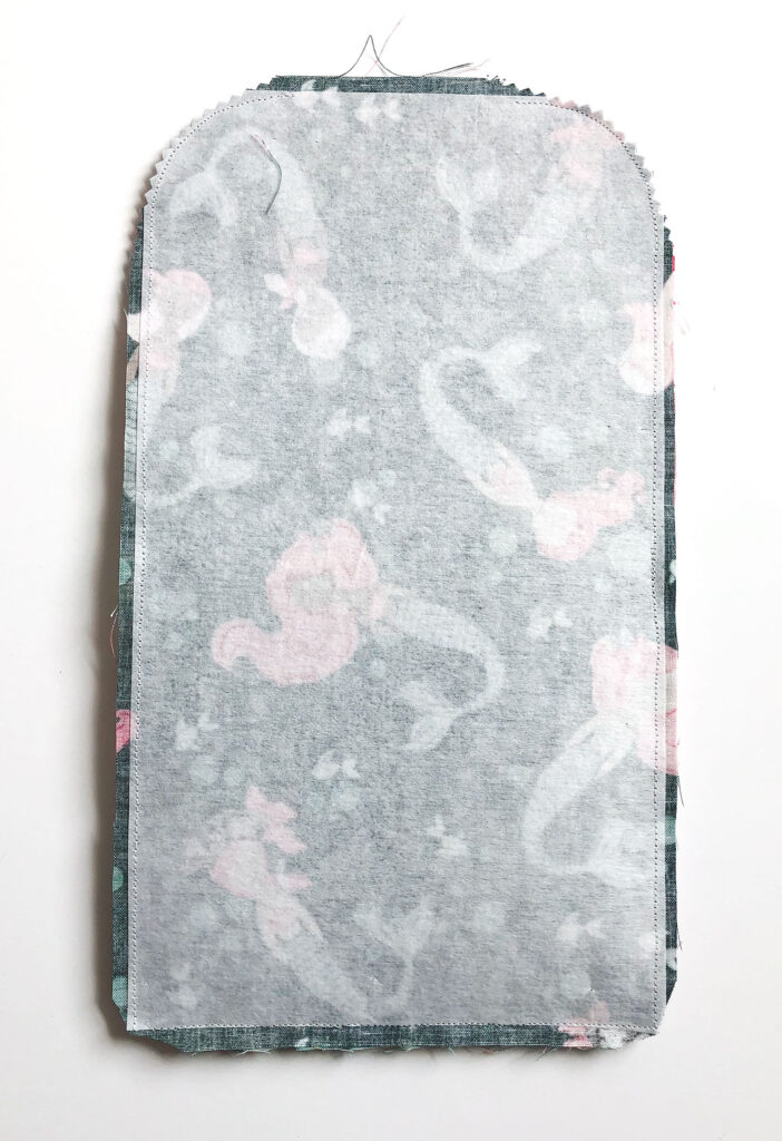 Sew a beautiful colored pencil pouch with top US sewing blog Ameroonie Designs. Image of sewn pouch with notches cut out of curved corners and seam allowance clipped at bottom corners.