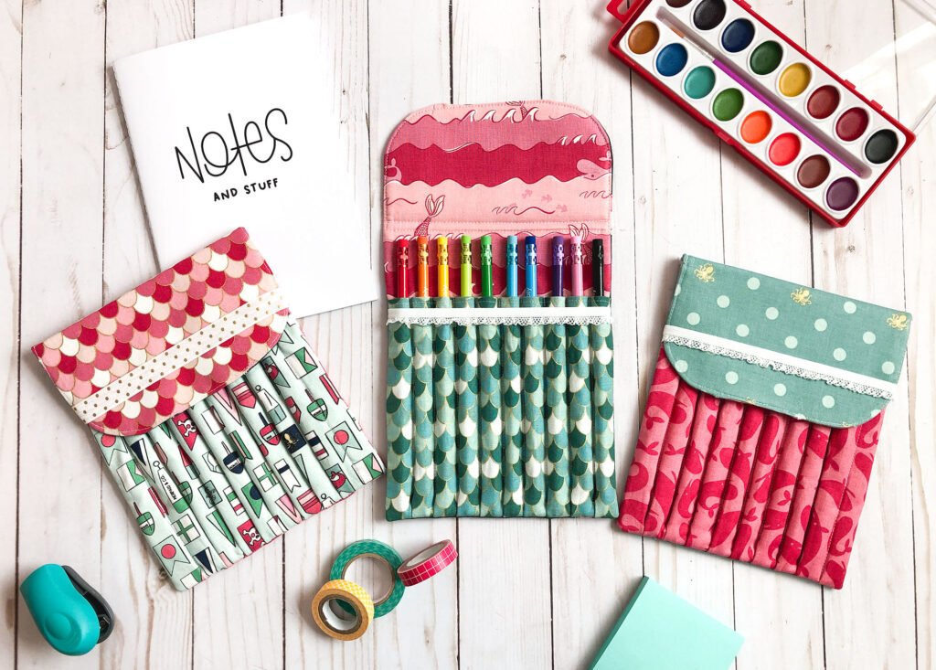 Sew a beautiful colored pencil pouch with top US sewing blog Ameroonie Designs. Image of colored pencil holder surrounded by notebook, watercolor paints and other office supplies.