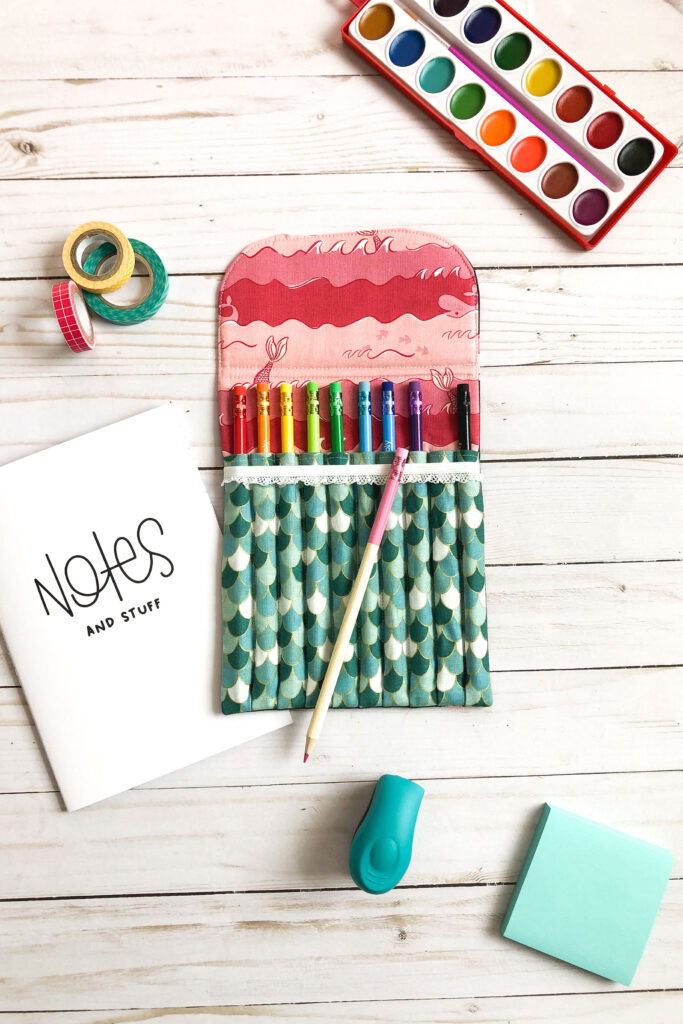 Sew a beautiful colored pencil pouch with top US sewing blog Ameroonie Designs. Image of filled colored pencil pouch with assorted school supplies.