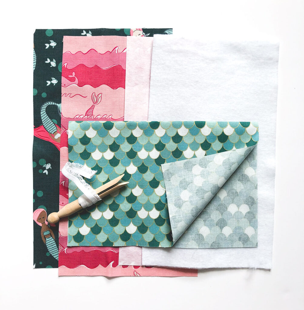 Sew a beautiful colored pencil pouch with top US sewing blog Ameroonie Designs. Image of fabric, fusible fleece, medium weight interfacing and elastic needed to sew pouch.
