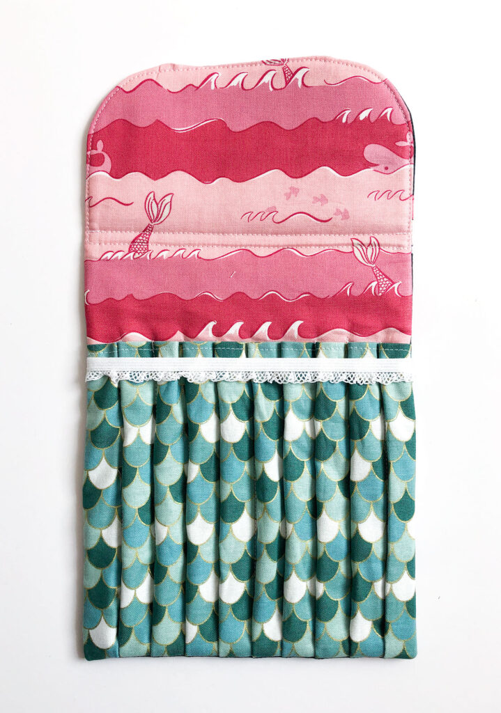Sew a beautiful colored pencil pouch with top US sewing blog Ameroonie Designs. Image of finished colored pencil pouch sewn with Ahoy Mermaids fabric.