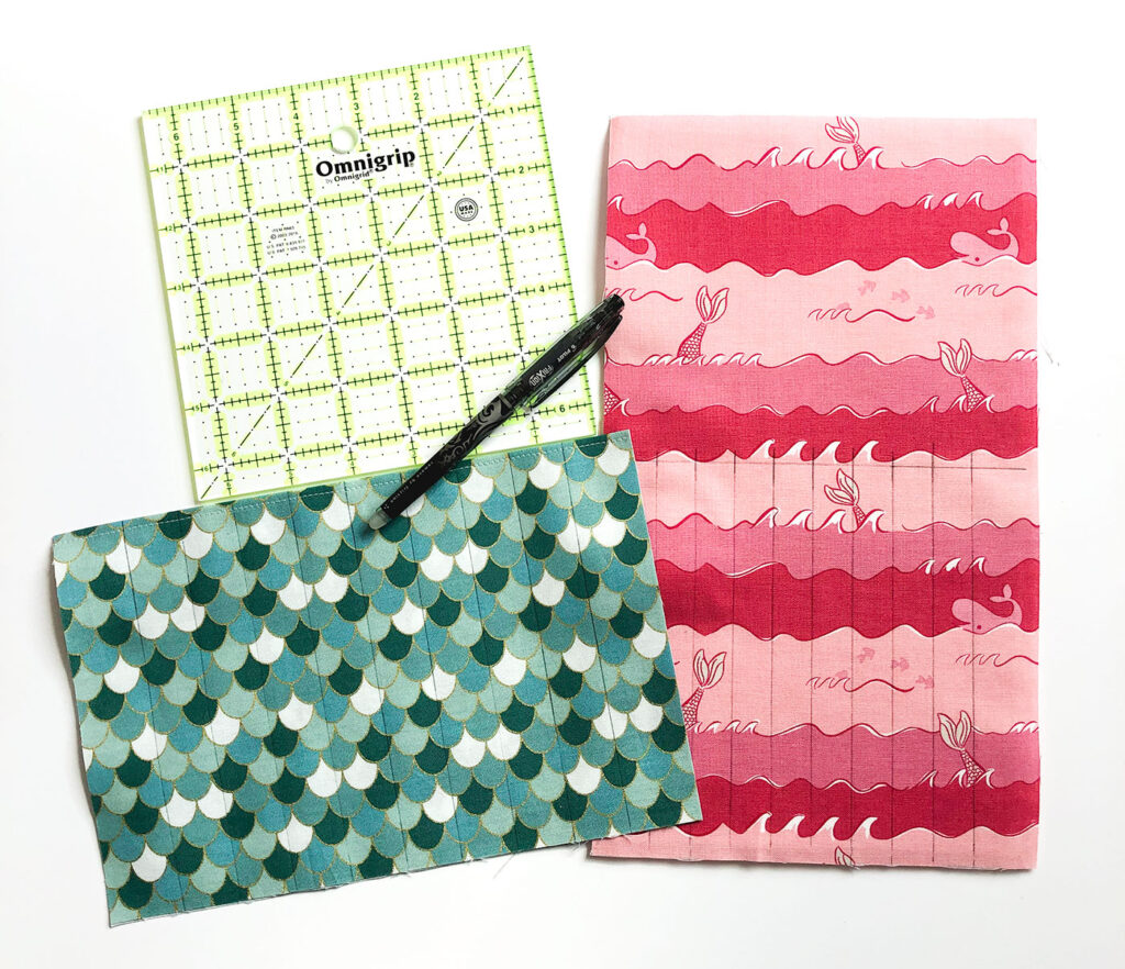 Sew a beautiful colored pencil pouch with top US sewing blog Ameroonie Designs. Image of pocket and backing fabrics marked with lines for making pencil pockets.